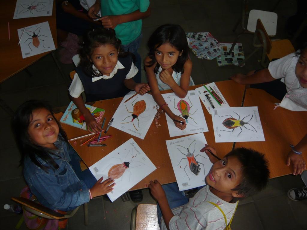 """Actividad en escuelas de El Salvador,  donde enseñan a los niños a identificar las """"chinches picudas""""."""